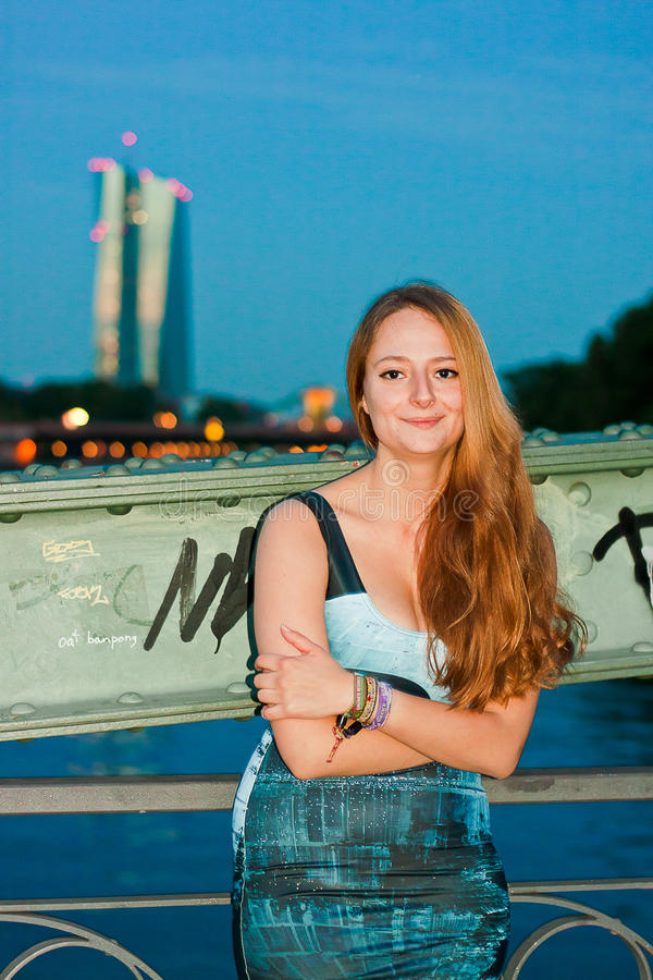 Donna sorridente davanti alla vista urbana di notte immagine stock