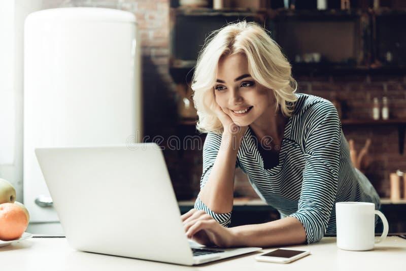 Donna sorridente dei giovani bella che per mezzo del computer portatile a casa immagine stock libera da diritti