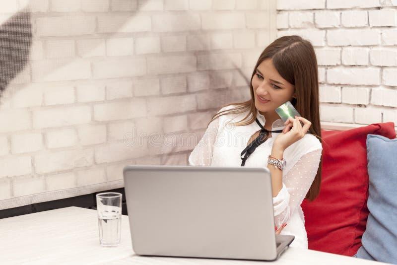 Donna sorridente dei giovani la bella usa il computer portatile e le carte di credito ai Bu immagine stock