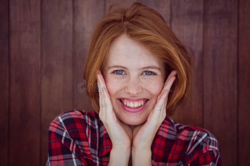 donna sorridente dei pantaloni a vita bassa con le sue mani sul suo fronte immagini stock libere da diritti