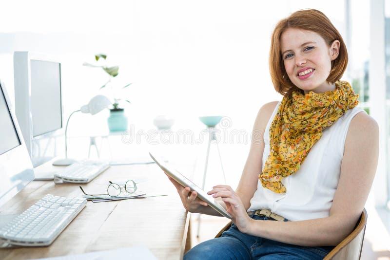 donna sorridente dei pantaloni a vita bassa su una compressa fotografia stock libera da diritti