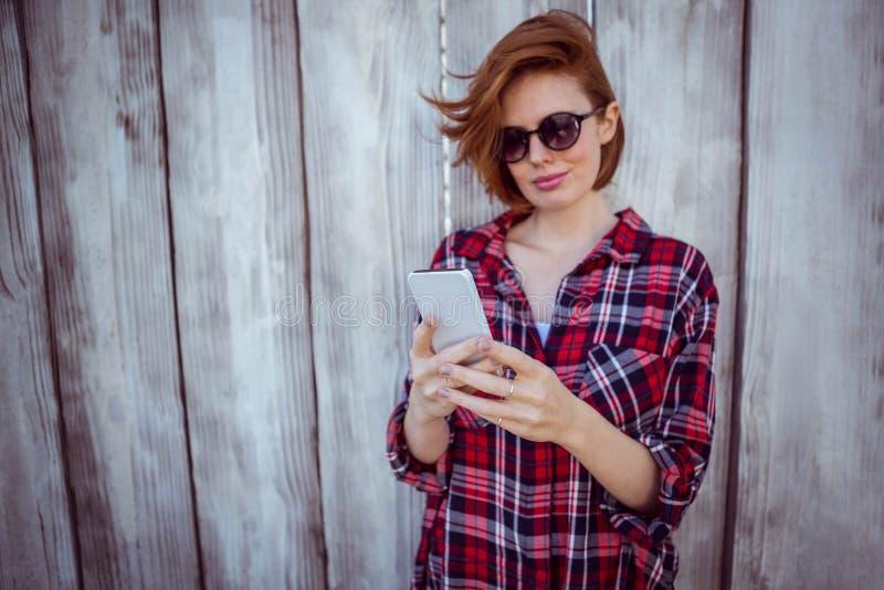 donna sorridente dei pantaloni a vita bassa sul suo smartphone immagini stock libere da diritti
