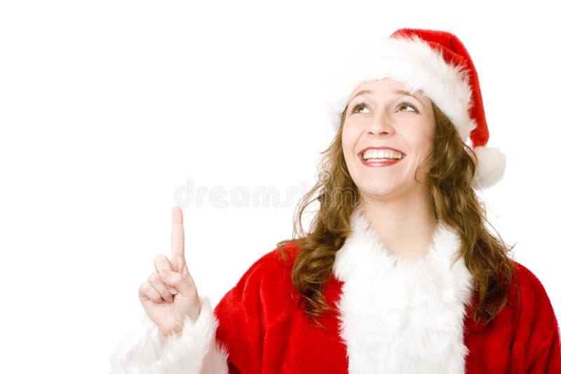 Donna sorridente del Babbo Natale che indica con la barretta in su immagine stock libera da diritti
