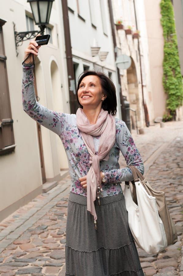 Donna sorridente del brunette con la macchina fotografica della foto in città fotografia stock libera da diritti