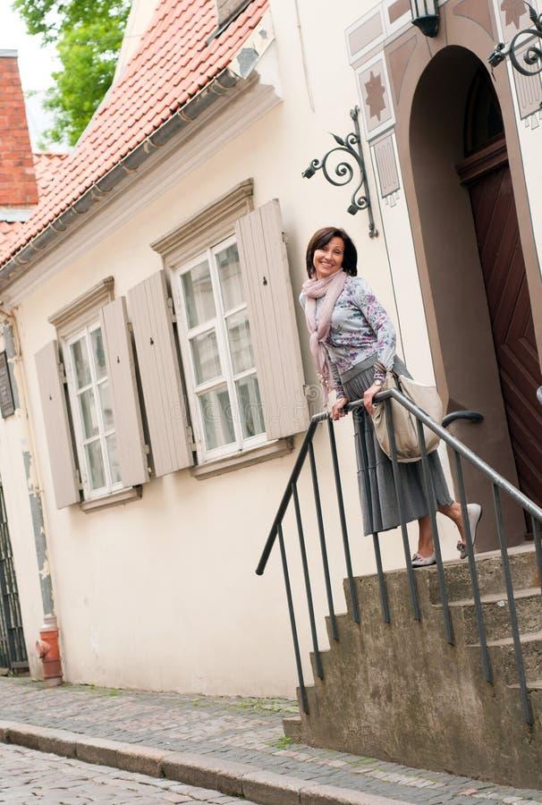 Donna sorridente del brunette in vecchia città immagine stock