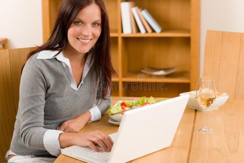 Donna sorridente del pranzo di funzionamento domestico con il computer portatile fotografie stock libere da diritti