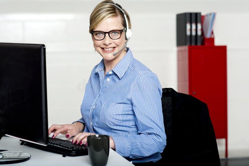 Donna sorridente del servizio d'assistenza che digita sulla tastiera fotografia stock