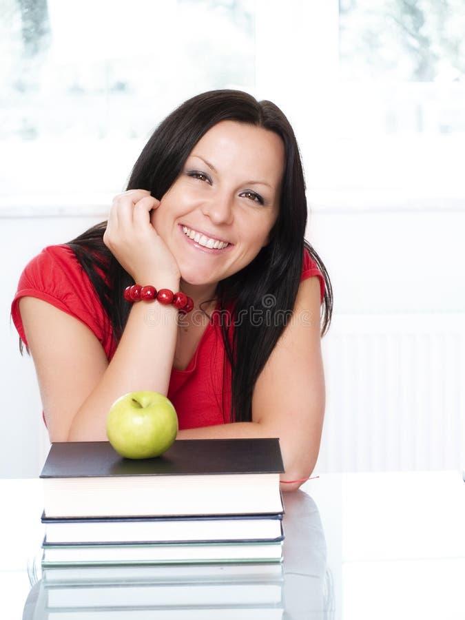 Donna sorridente dell'allievo con i libri ed il appl fotografia stock