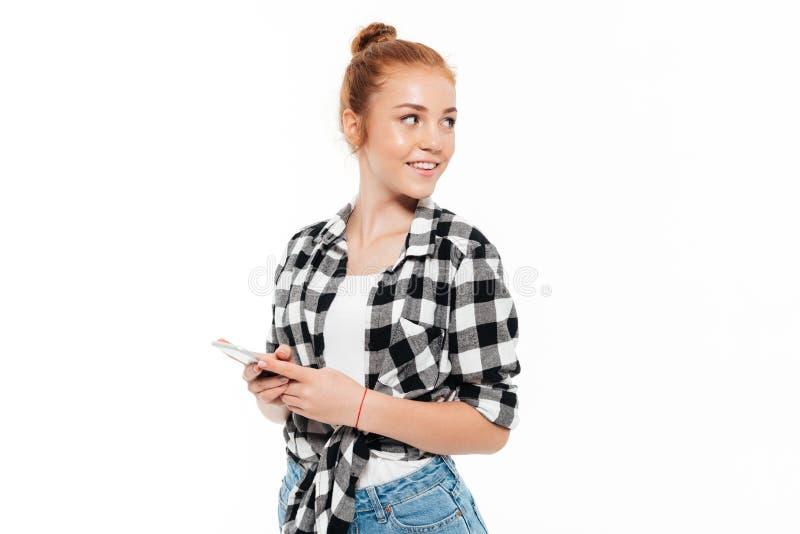 Donna sorridente dello zenzero in camicia e jeans che tengono smartphone immagine stock libera da diritti