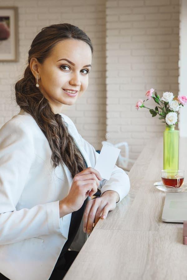 Donna sorridente di affari che mostra biglietto da visita Per i manifesti della pubblicità, immagini stock