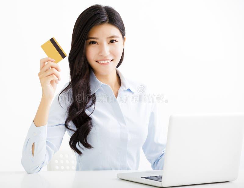 Donna sorridente di affari che mostra la carta di credito nell'ufficio fotografie stock