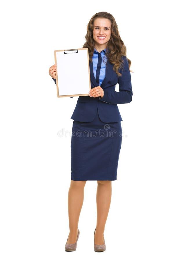 Donna sorridente di affari che mostra lavagna per appunti in bianco fotografia stock