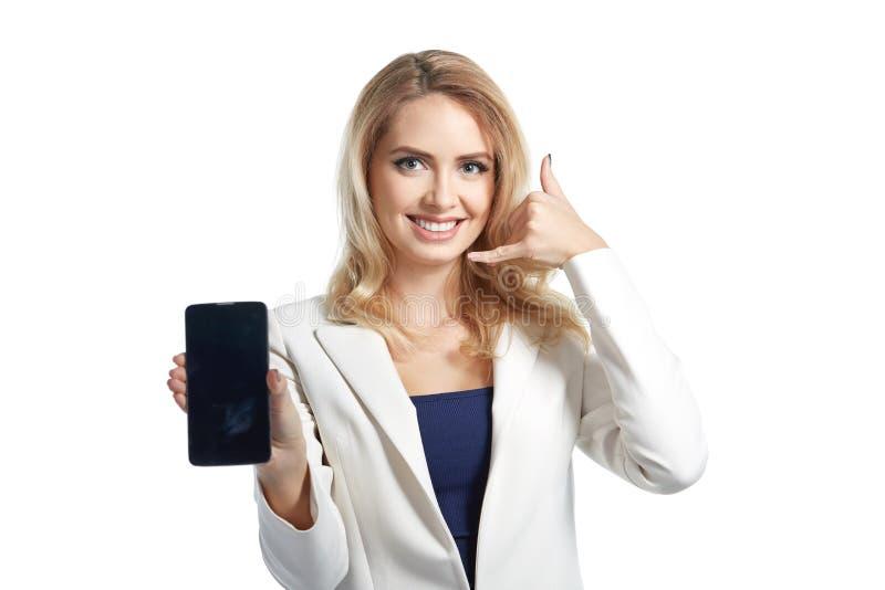Donna sorridente di affari che mostra un'esposizione del telefono e che mi rende ad una chiamata segno fotografia stock