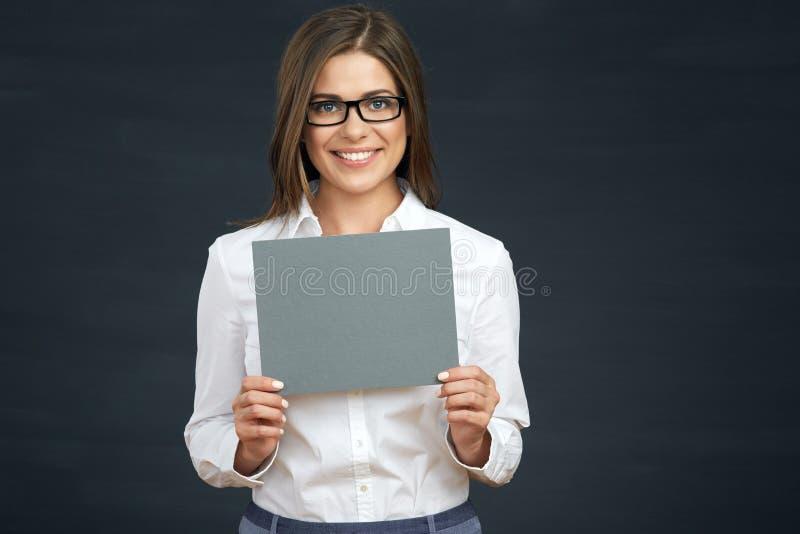 Donna sorridente di affari che tiene il bordo in bianco del segno immagine stock