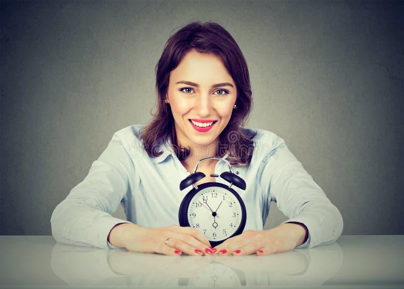 Donna sorridente di affari con la sveglia che si siede alla tavola fotografia stock