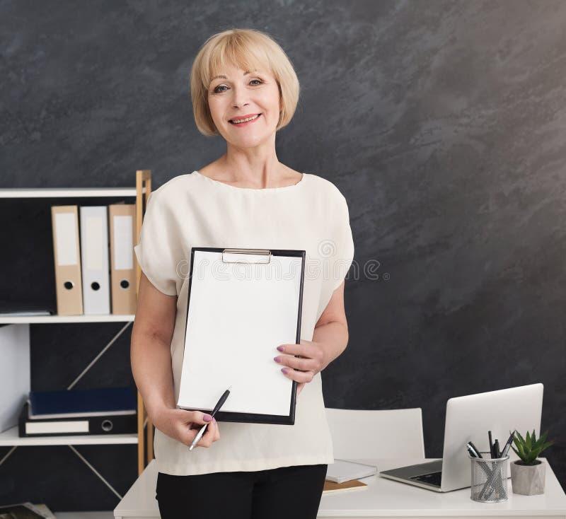 Donna sorridente di affari maturi che mostra lavagna per appunti in bianco immagine stock libera da diritti