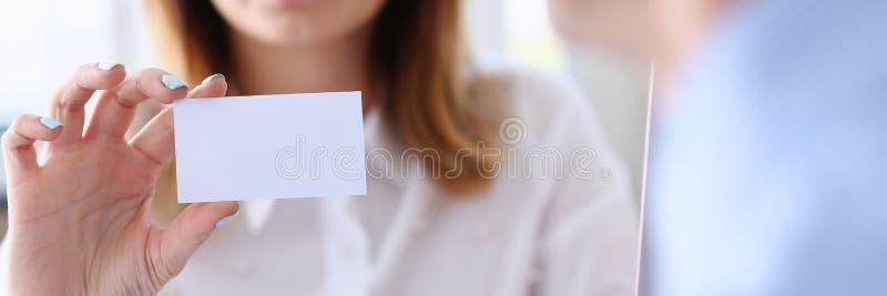 Donna sorridente di affari nella carta di chiamata in bianco della tenuta del vestito a disposizione fotografia stock