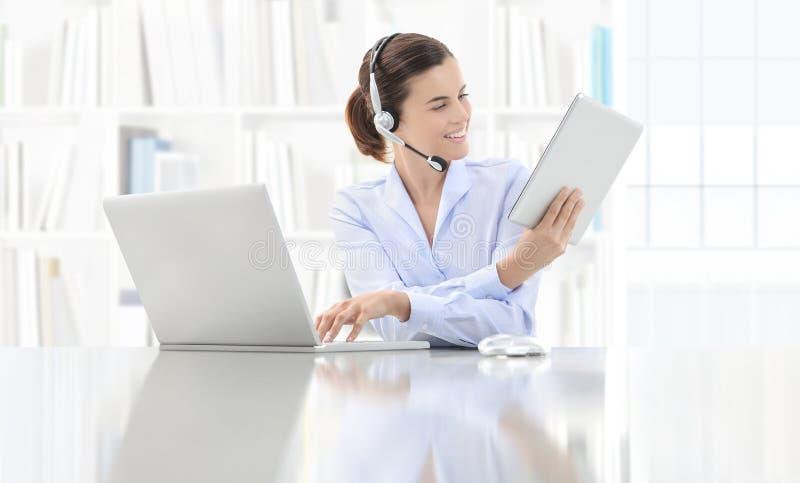 Donna sorridente di affari o un impiegato che lavora al suo spirito della scrivania fotografia stock libera da diritti
