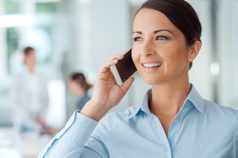 Donna sorridente di affari sul telefono immagini stock