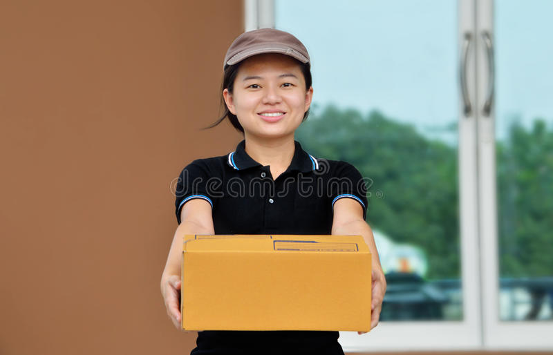 Donna sorridente di consegna, tenente il contenitore di cartone immagini stock libere da diritti