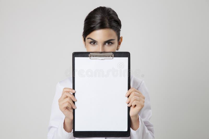 Donna sorridente di medico con lo spazio in bianco vuoto in mani fotografie stock libere da diritti