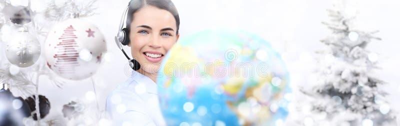 Donna sorridente di natale internazionale con il globo e la cuffia avricolare sopra immagini stock libere da diritti