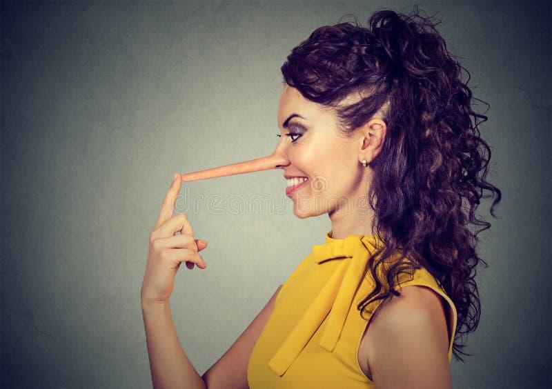 Donna sorridente di profilo laterale con il naso lungo Concetto del bugiardo fotografia stock libera da diritti