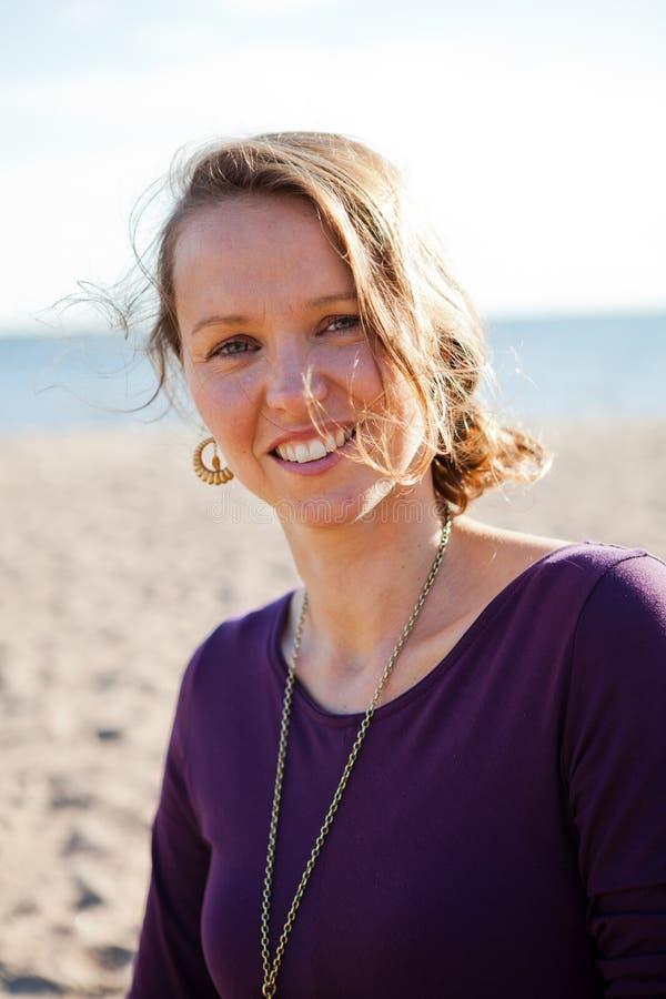 Donna sorridente felice alla spiaggia. fotografia stock