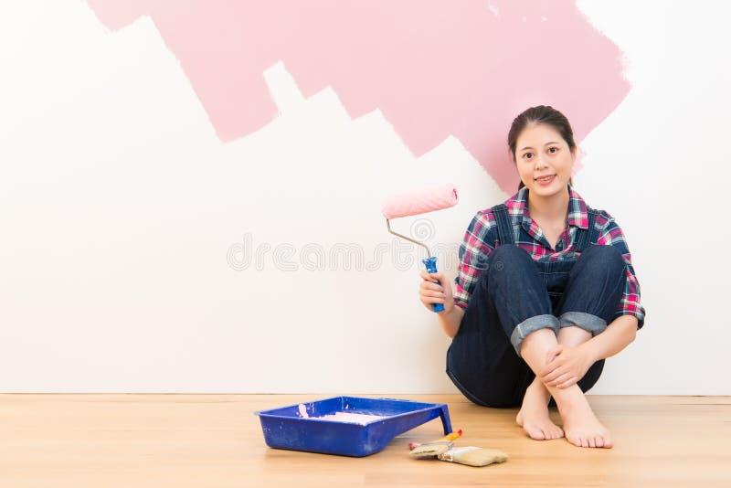 Donna sorridente felice che dipinge interna nel rosa fotografie stock