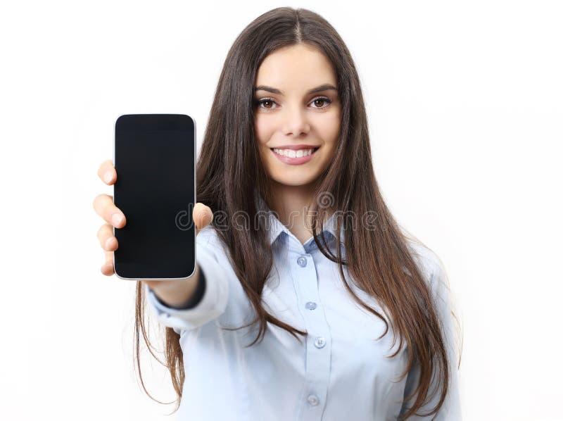 Donna sorridente felice che mostra telefono cellulare isolato nel bianco fotografia stock libera da diritti