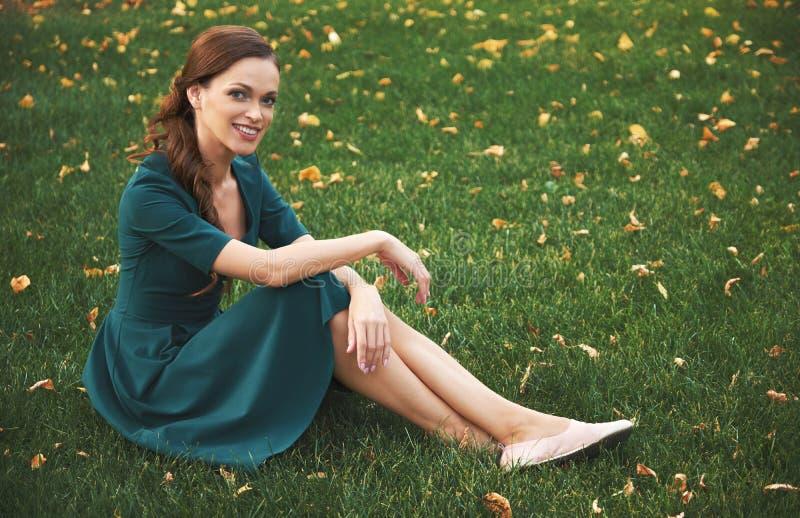 Donna sorridente felice che si siede su un'erba verde immagine stock