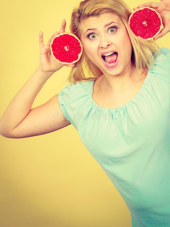 Donna sorridente felice che tiene pompelmo rosso fotografia stock