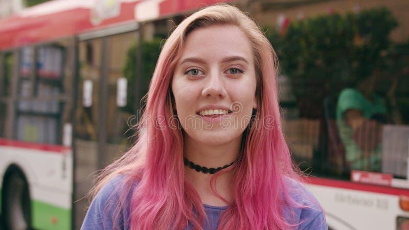 Donna sorridente felice con capelli rosa in città fotografia stock