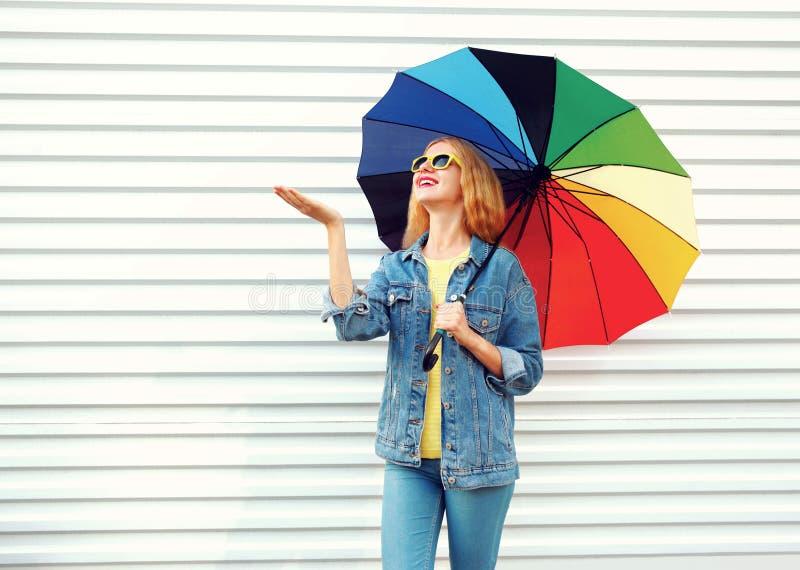 Donna sorridente felice con l'ombrello variopinto che controlla con la pioggia della mano tesa su bianco fotografia stock