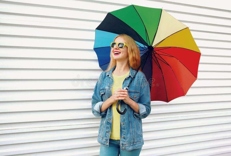 Donna sorridente felice del ritratto che tiene ombrello variopinto sulla parete bianca fotografie stock libere da diritti