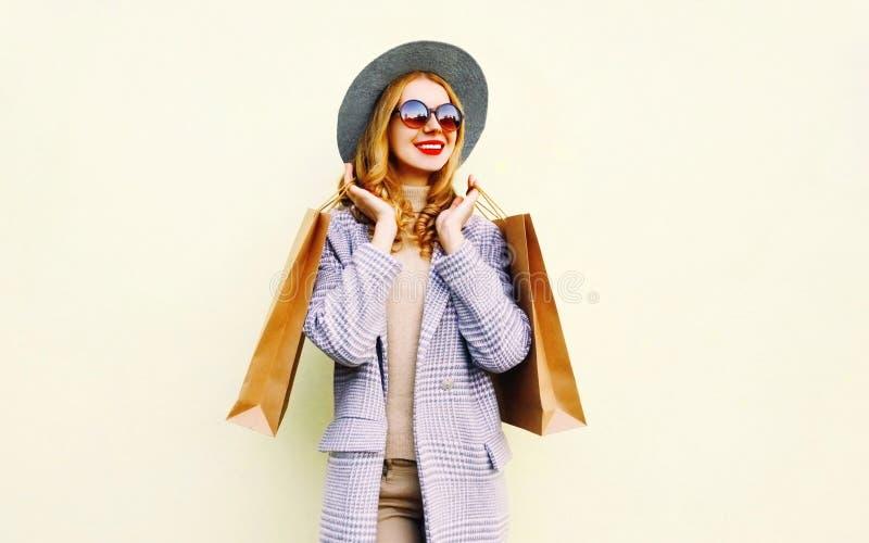 Donna sorridente felice del ritratto con i sacchetti della spesa in cappotto rosa, cappello rotondo su fondo immagini stock libere da diritti