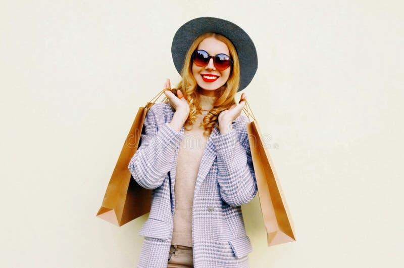 Donna sorridente felice del ritratto con i sacchetti della spesa in cappotto rosa, cappello rotondo su fondo fotografie stock libere da diritti