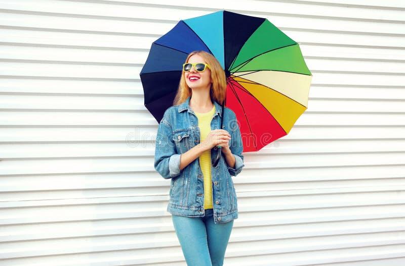 Donna sorridente felice del ritratto con l'ombrello variopinto, sogni distogliente lo sguardo sul bianco immagine stock libera da diritti