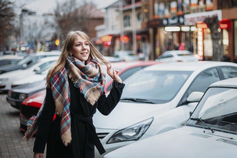 Donna sorridente felice giovane in cappotto e sciarpa neri che cammina intorno alla città Aspettando il suo ragazzo Riunione aspe fotografia stock libera da diritti