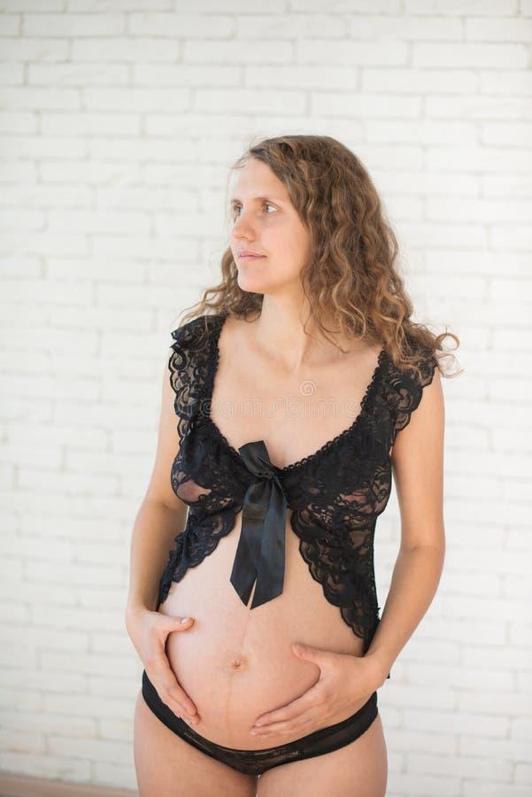 Donna sorridente felice incinta che si siede su un sofà fotografia stock libera da diritti