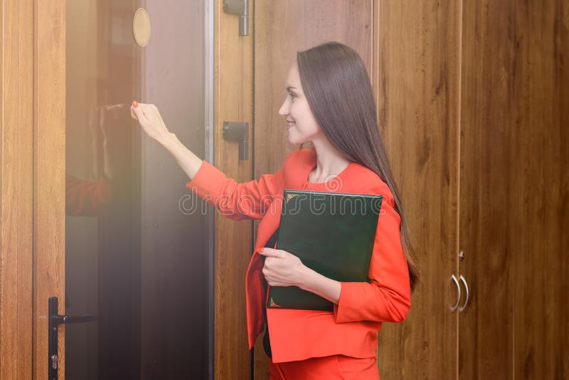 Donna sorridente felice in un vestito rosso con i documenti a disposizione che battono alla porta al capo immagini stock libere da diritti