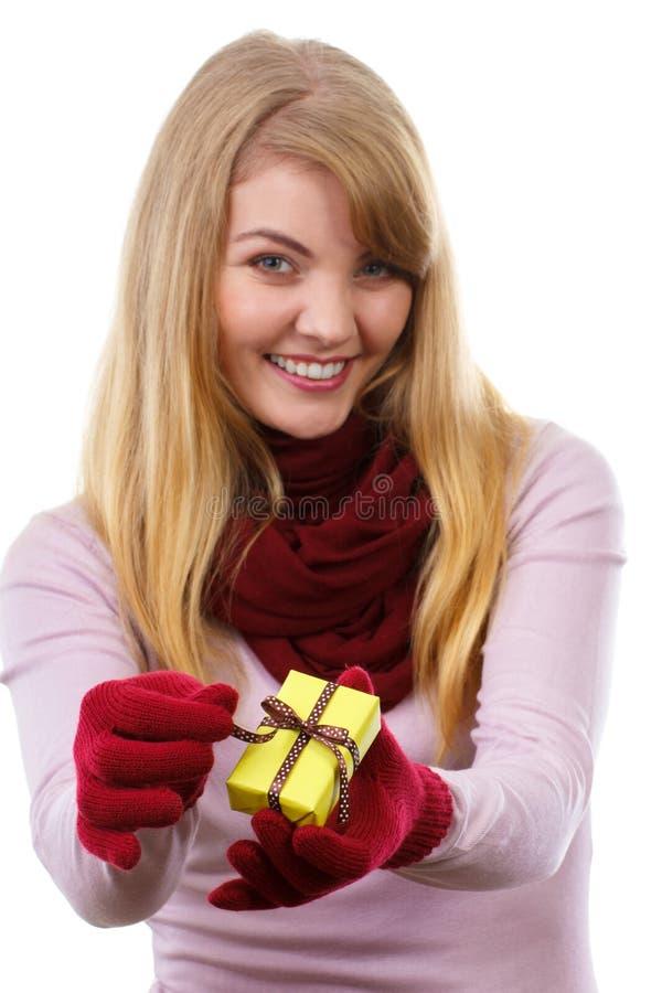 Donna sorridente in guanti di lana che aprono regalo per il Natale o l'altra celebrazione fotografie stock
