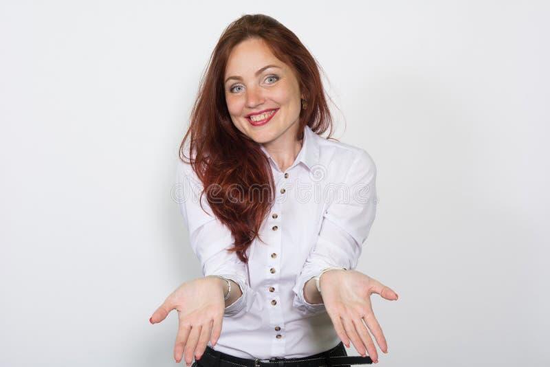Donna sorridente in leggera mani da parte divorziate una blusa isolate sopra un fondo bianco fotografia stock