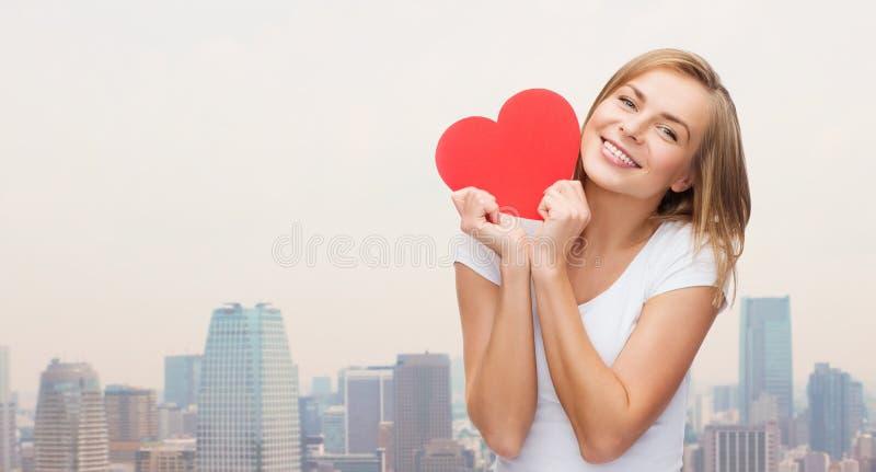 Donna sorridente in maglietta bianca che tiene cuore rosso immagine stock