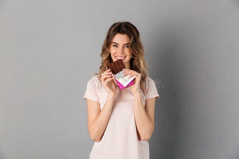 Donna sorridente in maglietta che mangia cioccolato ed esame della macchina fotografica fotografia stock libera da diritti