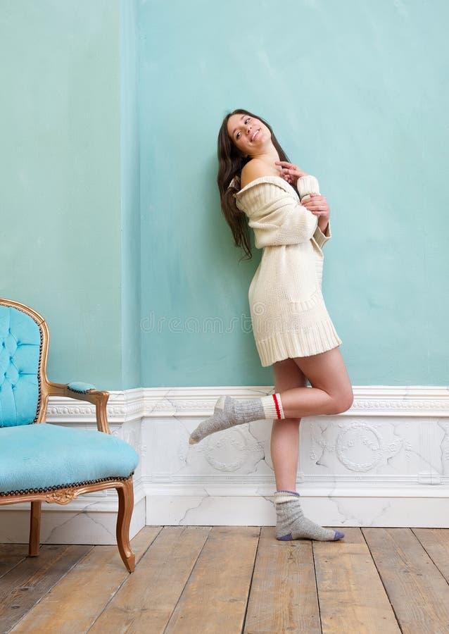 Donna sorridente in maglione e calzini che stanno all'interno fotografia stock