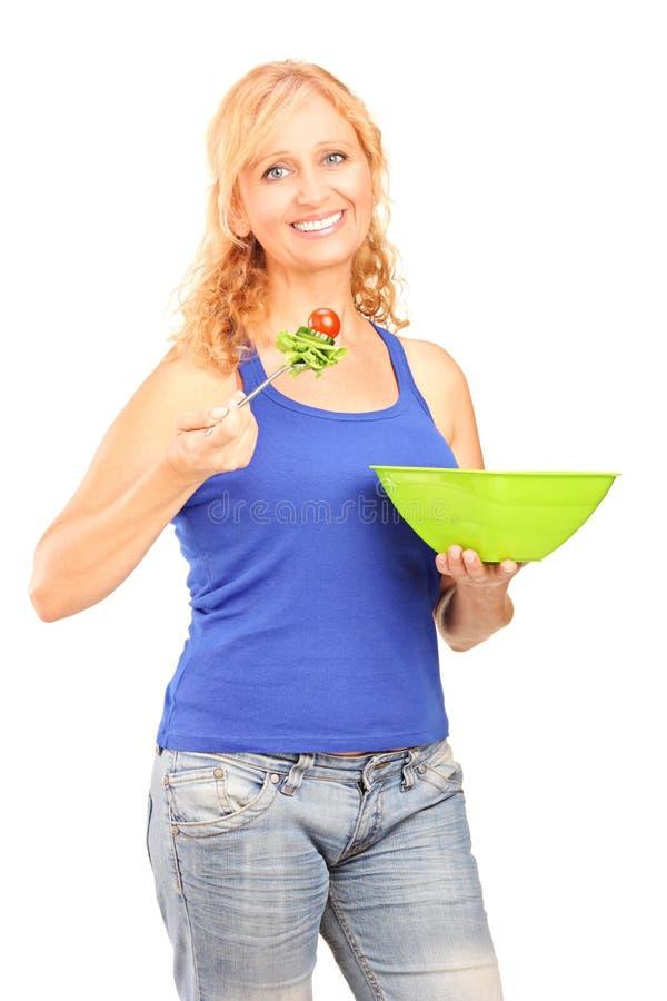 Donna sorridente matura che mangia un'insalata fotografia stock libera da diritti