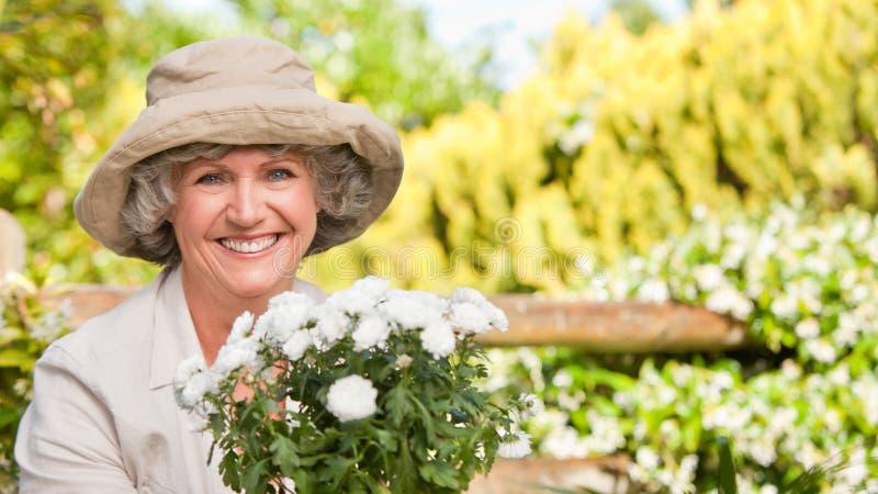 Donna sorridente nel suo giardino fotografia stock
