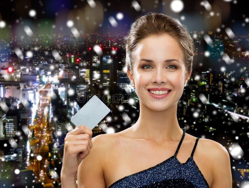 Donna sorridente nella carta di credito della tenuta del vestito da sera immagine stock