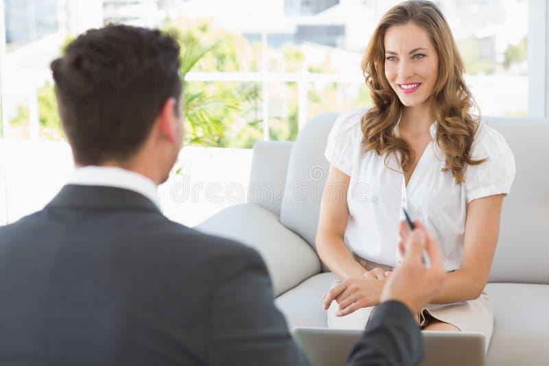 Donna sorridente nella riunione con un consulente finanziario immagine stock